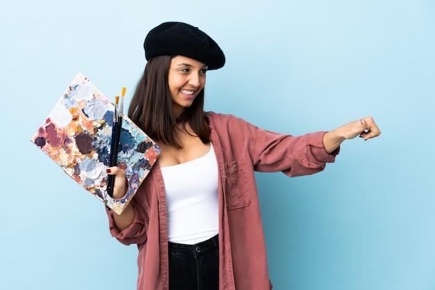 Mujer joven artista sosteniendo una paleta en azul aislado dando un gesto de pulgares arriba