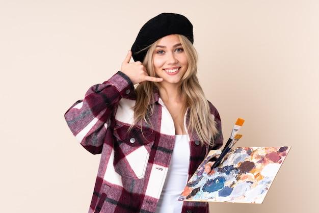 Mujer joven artista sosteniendo una paleta con pintura