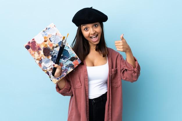Mujer joven artista sosteniendo una paleta sobre azul aislado dando un gesto de pulgares arriba