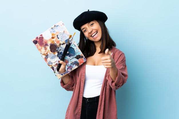 Mujer joven artista sosteniendo una paleta sobre azul aislado con los pulgares hacia arriba porque algo bueno ha sucedido.