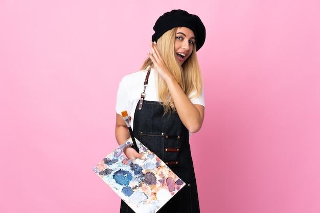 Mujer joven artista sosteniendo una paleta sobre pared rosa aislada escuchando algo