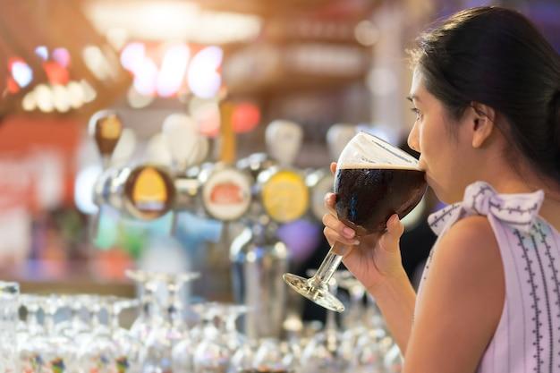Mujer joven de asia que bebe la cerveza negra mientras que fija en la barra contraria.