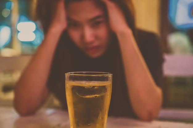 Mujer joven asiática en acción solitaria y deprimida y sosteniendo la cabeza en las manos y ver el vidrio o