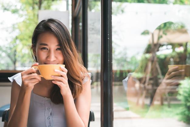 Mujer joven asiática alegre que bebe el café o el té caliente que lo goza mientras que se sienta en café