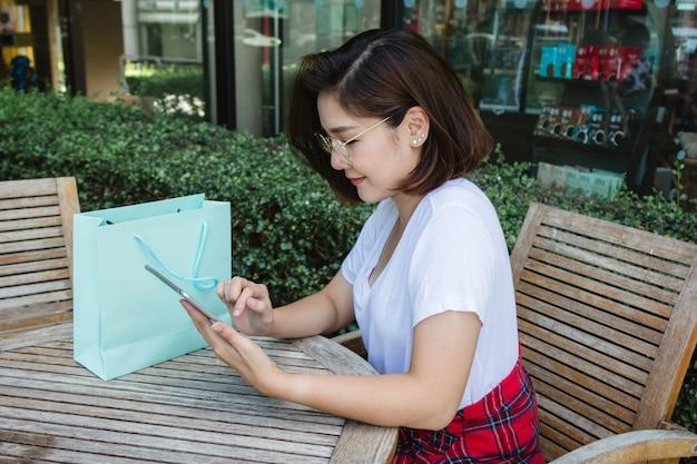 Mujer joven asiática alegre que se sienta en café usando el smartphone para hablar, leer y mandar un sms