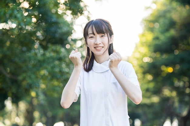 Mujer joven asiática con una bata blanca haciendo una pose de tripas