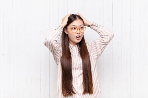 Mujer joven asiática con la boca abierta, con aspecto horrorizado y conmocionado por un terrible error, levantando las manos a la cabeza