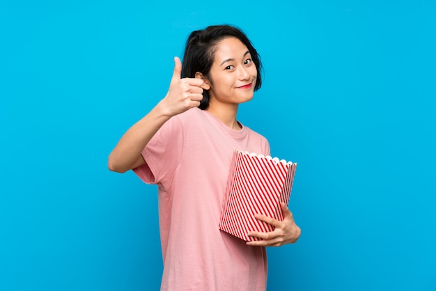 Mujer joven asiática comiendo palomitas de maíz con el pulgar hacia arriba porque algo bueno ha sucedido.
