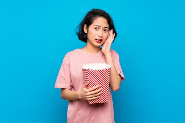 Mujer joven asiática comiendo palomitas de maíz con sorpresa y expresión facial conmocionada