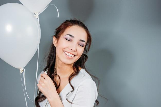 Mujer joven asiática feliz hermosa con el pelo largo oscuro con los globos blancos
