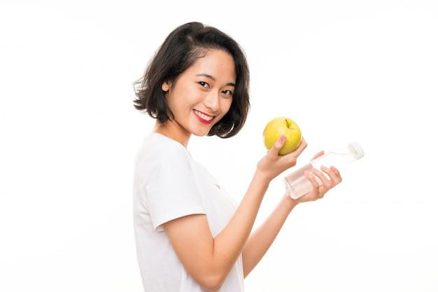 Mujer joven asiática con una manzana y una botella de agua