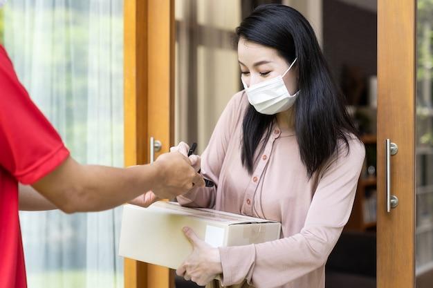 Mujer joven asiática con mascarilla que recibe el paquete y el signo del repartidor de manos en la puerta.