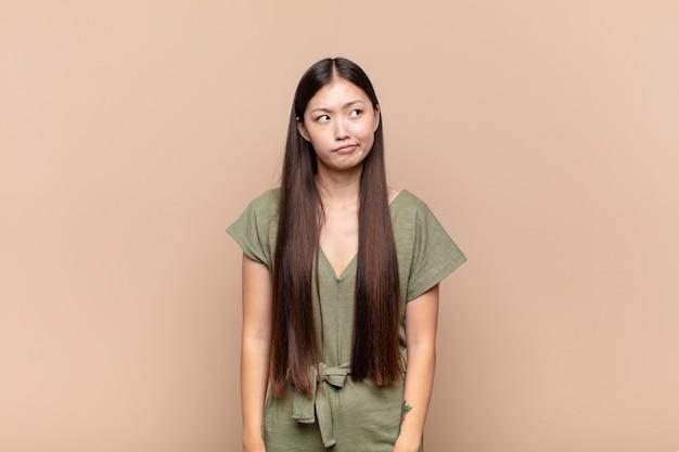 Mujer joven asiática mirando perplejo y confundido aislado