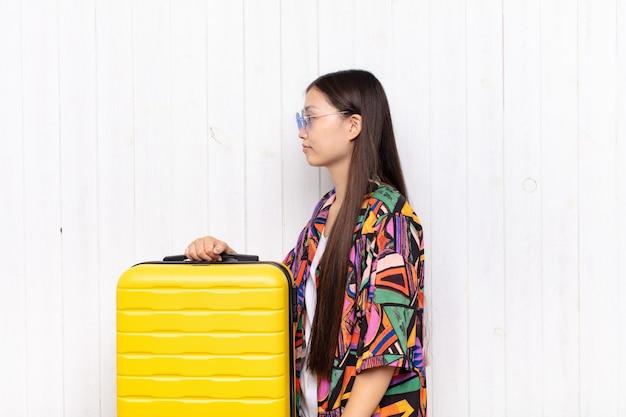 Mujer joven asiática en perfil con equipaje