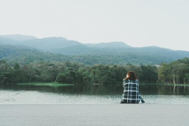 Mujer joven asiática de pie frente al mar
