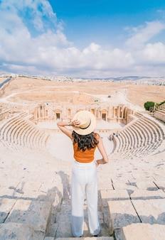 Mujer joven asiática de pie frente al teatro romano del sur, jerash, jordania