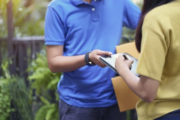 Mujer joven asiática que firma en la tableta, entrada de su hogar.