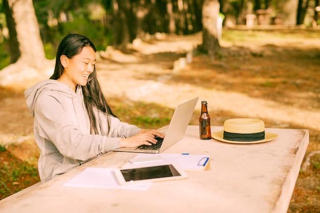 Mujer joven asiática que mecanografía en el ordenador portátil que se sienta en el escritorio en parque
