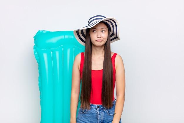 Mujer joven asiática que parece perpleja y confundida, preguntándose o tratando de resolver un problema o pensando