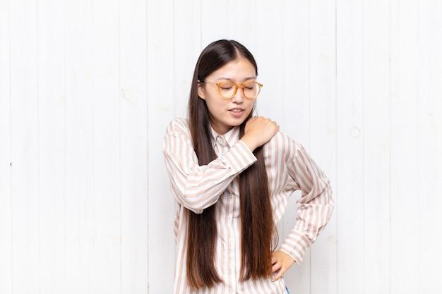 Mujer joven asiática que se siente cansada, estresada, ansiosa, frustrada y deprimida, que sufre de dolor de espalda o cuello