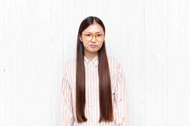 Mujer joven asiática que se siente confundida y dudosa, preguntándose o tratando de elegir o tomar una decisión