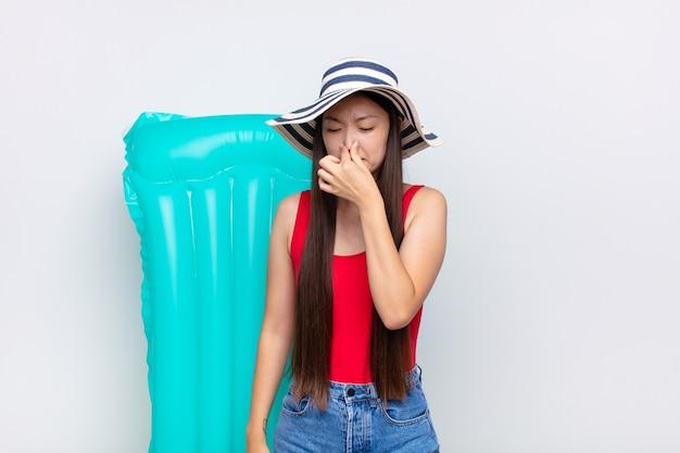 Mujer joven asiática que se siente disgustada, tapándose la nariz para evitar oler un hedor desagradable y desagradable. concepto de verano