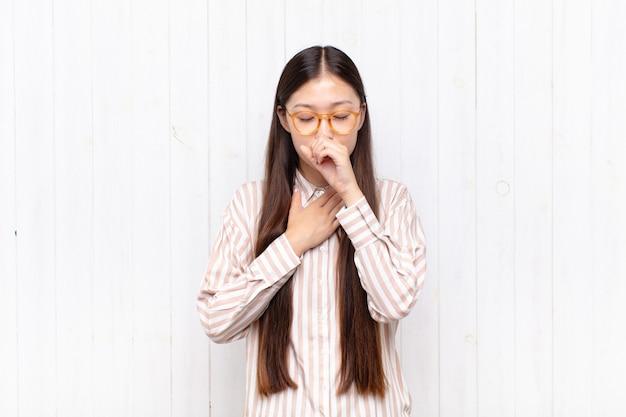 Mujer joven asiática que se siente enferma con dolor de garganta y síntomas de gripe, tos con la boca cubierta
