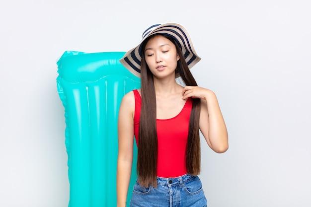 Mujer joven asiática que se siente estresada, ansiosa, cansada y frustrada, tirando del cuello de la camisa, luciendo frustrada con el problema. concepto de verano