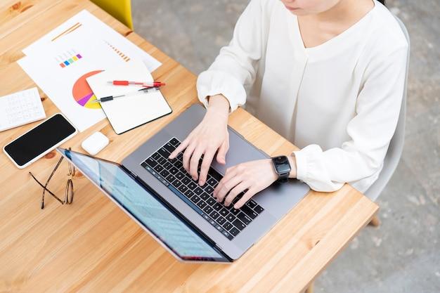 Mujer joven asiática que trabaja con una computadora portátil