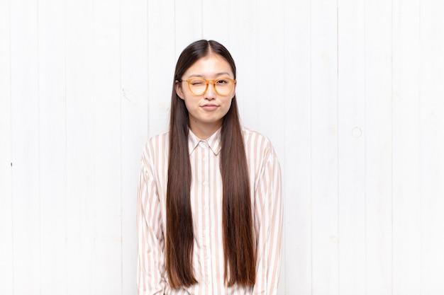 Mujer joven asiática que se ve feliz y amigable, sonriendo y guiñando un ojo con una actitud positiva
