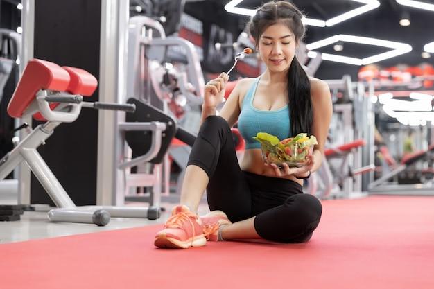 Mujer joven asiática sana que come la ensalada verde de las verduras en el gimnasio.