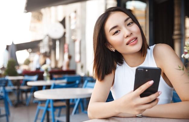 Mujer joven asiática sentada en la cafetería con teléfono móvil, mirando a la cámara soñadora