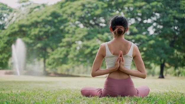 Mujer joven asiática sentada en la hierba en posición de loto