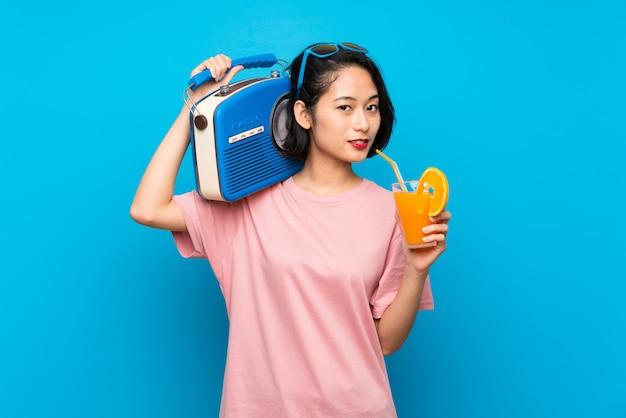Mujer joven asiática sobre azul aislado que sostiene una radio