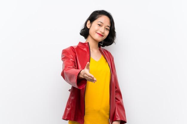 Mujer joven asiática sobre blanco aislado agitando las manos para cerrar un buen trato