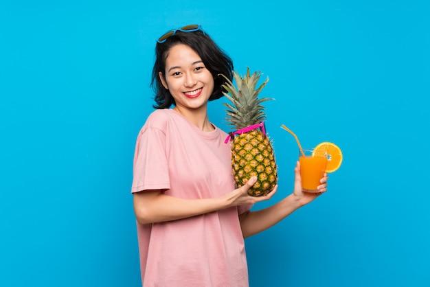 Mujer joven asiática sobre el fondo azul aislado que sostiene una piña con las gafas de sol
