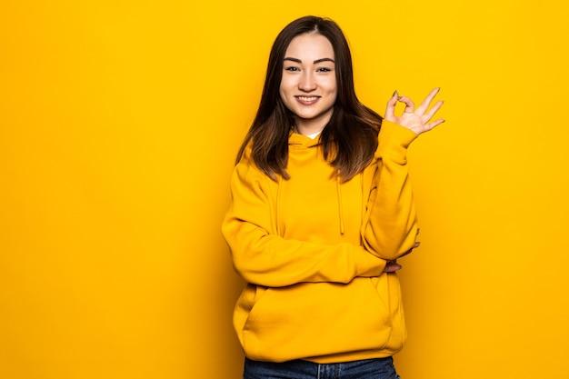 Mujer joven asiática sobre pared amarilla aislada que muestra el signo de ok y el pulgar hacia arriba gesto