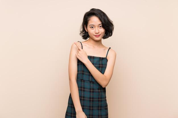 Mujer joven asiática sobre la pared amarilla aislada que señala al lado para presentar un producto