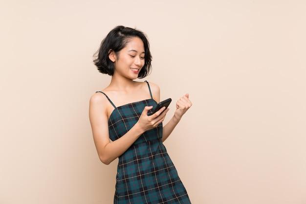 Mujer joven asiática sobre la pared amarilla aislada con el teléfono en la posición de la victoria