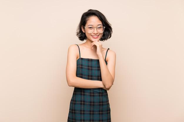 Mujer joven asiática sobre la pared amarilla aislada con los vidrios y la sonrisa