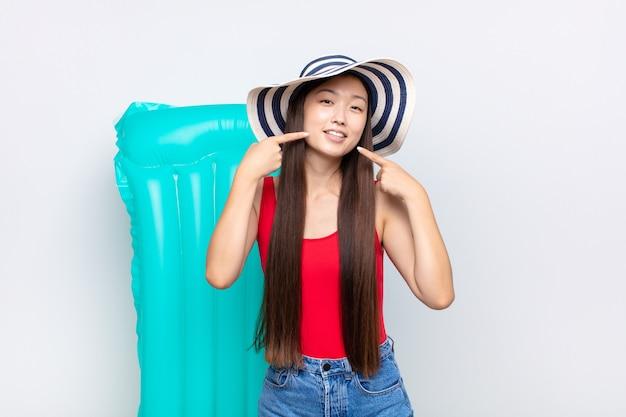 Mujer joven asiática sonriendo con confianza apuntando a su propia sonrisa amplia, actitud positiva, relajada y satisfecha. concepto de verano