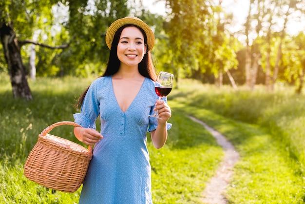 Mujer joven asiática con vidrio y cesta