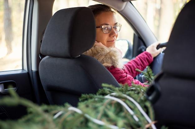 Mujer joven en el asiento del conductor en un coche mirando a la cámara con árbol de navidad en los asientos traseros