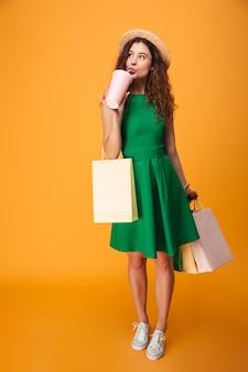 Mujer joven asombrosa que bebe el agua aireada que sostiene bolsos de compras.