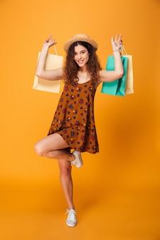 Mujer joven asombrosa que sostiene bolsos de compras.