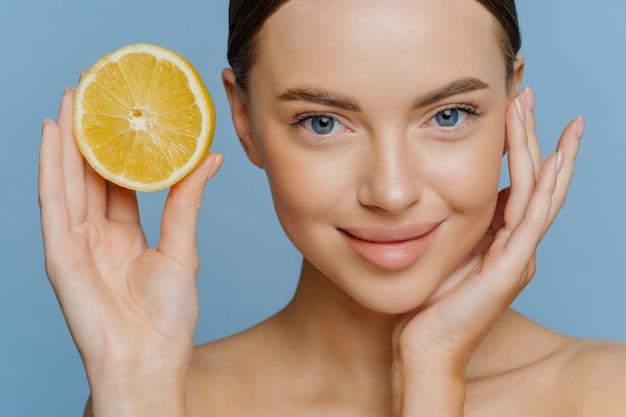 Una mujer joven de aspecto agradable toca la cara suavemente tiene una tez bien cuidada, una piel radiante y saludable