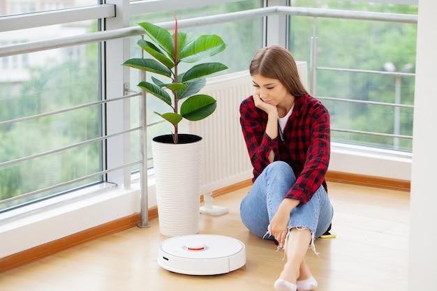 Mujer joven con aspiradora automática para limpiar el piso.