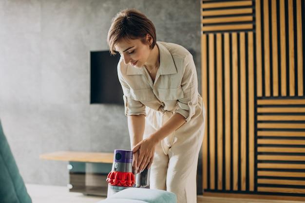 Mujer joven con aspiradora recargable limpiando en casa