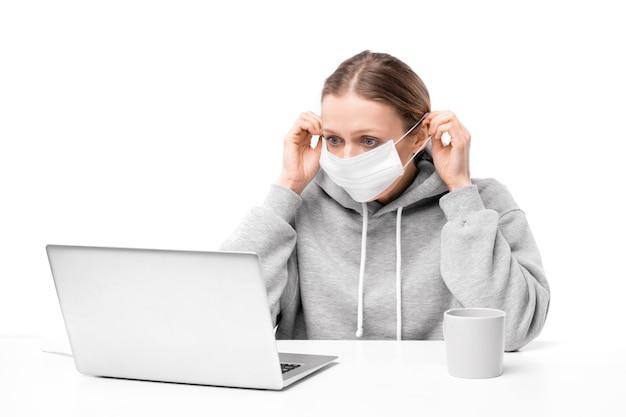 Mujer joven asustada con coronavirus ajustando mascarilla y leyendo noticias en la computadora portátil