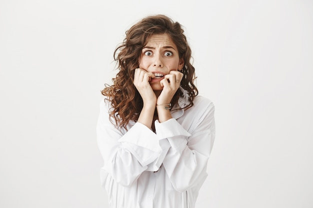Mujer joven asustada mordiéndose las uñas, temblando de miedo